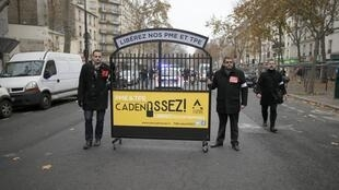 Passeata do patronato nas ruas de Paris levando um portão com os dizeres: Libertem nossas empresas algemadas.