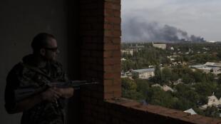 Пророссийский сепаратист наблюдает за дымом, поднимающимся над аэропортом в Донецке, 23 сентября 2014 г.
