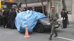 Police cover Mostafa Ahmadi Roshan's car after the blast