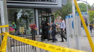Canada- Toronto : Cảnh sát vào quán cà phê bị hư hại sau vụ nổ súng. Ảnh 23/07/2018.