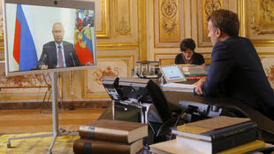 French President Emmanuel Macron talks to Russian President Vladimir Putin during a video conference Friday, June 26, 2020 at the Elysee Palace in Paris.