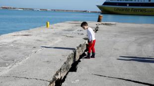 Menino observa estragos do terremoto em Zakynthos, no mar Jônico