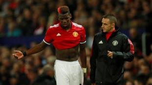 Le joueur Paul Pogba sort du terrain, suite à sa blessure, lors du match Manchester United - Bâle, le 12 septembre 2017.