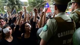 Mujeres vestidas de negro protestan ante la policía chilena por la muerte de una veintena de personas durante las protestas sociales en Chile, el 1º de noviembre de 2019
