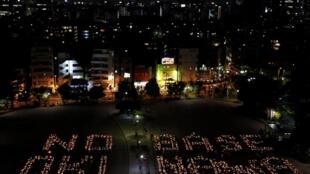 """東京示威民眾用燭光組成英文字""""沖繩不要軍事基地"""". (25/4/2010)"""