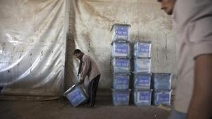 Afghan man carries a ballot box at a warehouse in Afghanistan's Independent Election Commission in Kabul