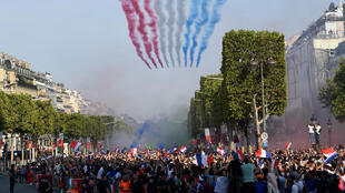 Air Force planes fly overhead at the team drives down the Champs Elysées