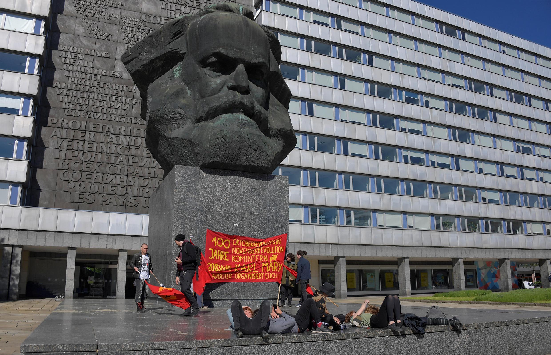 Ativistas de esquerda aos pés do monumento de Karl Marx, após um protesto contra a manifestação de grupos de extrema-direita alemães em Chemnitz, Alemanha, em 1º de maio de 2018.