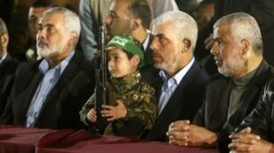 Le nouveau leader du Hamas de la bande de Gaza, Yahya Sinwar (2e Droite) avec sur ses genoux le fils de  Mazen Foqaha lors des funérailles de ce chef militaire du Hamas.