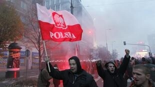 A demonstrator holds up a flag as violence breaks out at a parade celebrating Poland's national holiday in Warsaw, 11 November, 2012