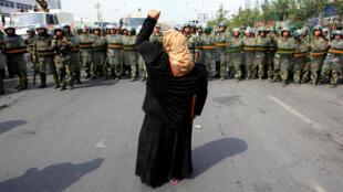 資料圖片:2009年7月7日,烏魯木齊一名婦女向前來應對當地抗議集會的防暴警察怒吼。