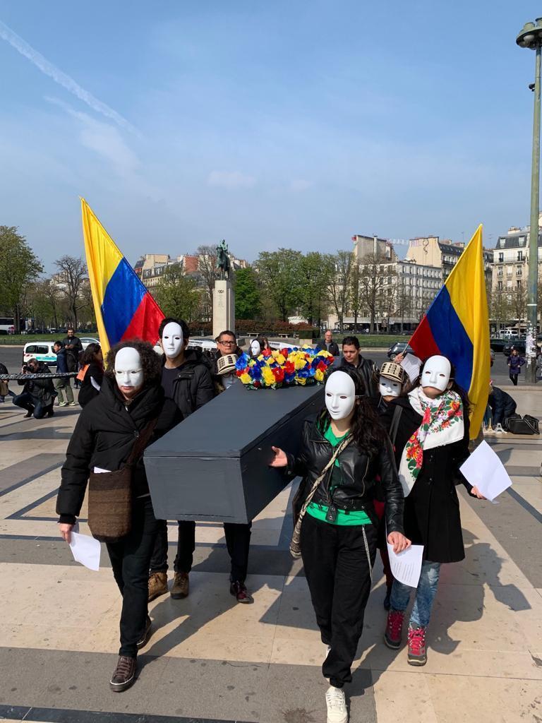 Cubiertos con máscaras blancas, los manifestantes formaron un cortejo encabezado por un ataúd con flores de los colores de la bandera colombiana.