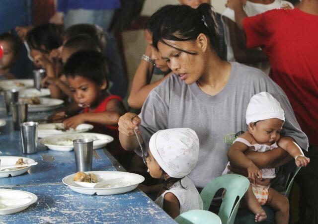 Un mère nourrit ses enfants durant un programme d'alimentation financé par une ONG. Photo, le 31 janvier 2012.
