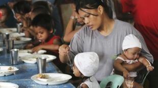 Una madre da de comer a sus hijos gracias a un programa de ayuda financiado por una ONG en Filipinas, el 31 de enero de  2012.