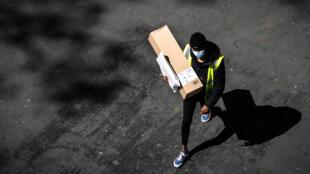 Un livreur masqué porte un colis Amazon et une enveloppe dans les rues de Paris, le 15 avril 2020, au 30e jour du confinement.