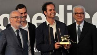 O artista Tino Sehgal, com o Leão de Ouro nas mãos, ao lado dos organizadores da Bienal de Veneza, em 2 de junho de 2013.