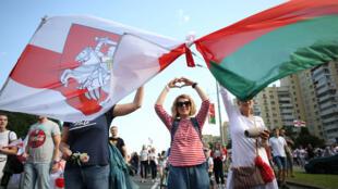 Belarus: Đối lập phản đối kết quả bầu cử, Minsk, 30/08/2020. Trong ảnh, người biểu tình kết chặt hai quốc kỳ Belarus, quốc kỳ hiện tại (P) và quốc kỳ đầu tiên của Belarus độc lập Trắng-Đỏ-Trắng.