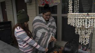 Karla Pérez y Esperanza González se calientan junto a una parrilla durante el corte de energía eléctrica causado por la ola de frío el 16 de febrero de 2021 en Houston, Texas.