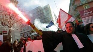 Un avocat tient une fusée de detresse lors de la 36e journée consécutive de grève contre les plans de réforme des retraites du gouvernement à Nice, le 9 janvier 2020.