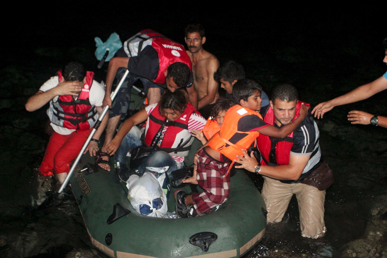 Migrantes desembarcam de um bote após chegar à ilha grega de Kos.