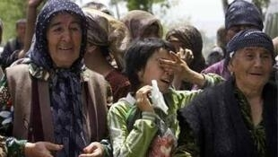 Ethnic Uzbek refugees cry while waiting for permission to move to Uzbekistan at the border between Kyrgyzstan and Uzbekistan near the city of Osh, 16 June, 2010