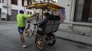 """Một phu """"xích lô"""" đang kéo xe chở khách du lịch có cắm lá cờ Mỹ trên đường phố La Habana, 18/12/2014."""
