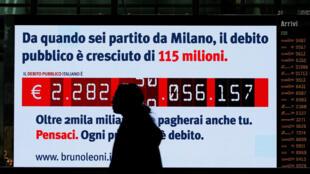 Une femme passe devant un écran qui égrène en temps réel la dette publique italienne à la gare centrale de Termini, le 15 février 2018.