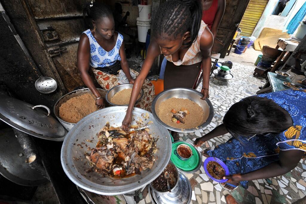 Une femme prépare un plat de riz et de poisson dans un restaurant de rue de Dakar (image d'illustration).