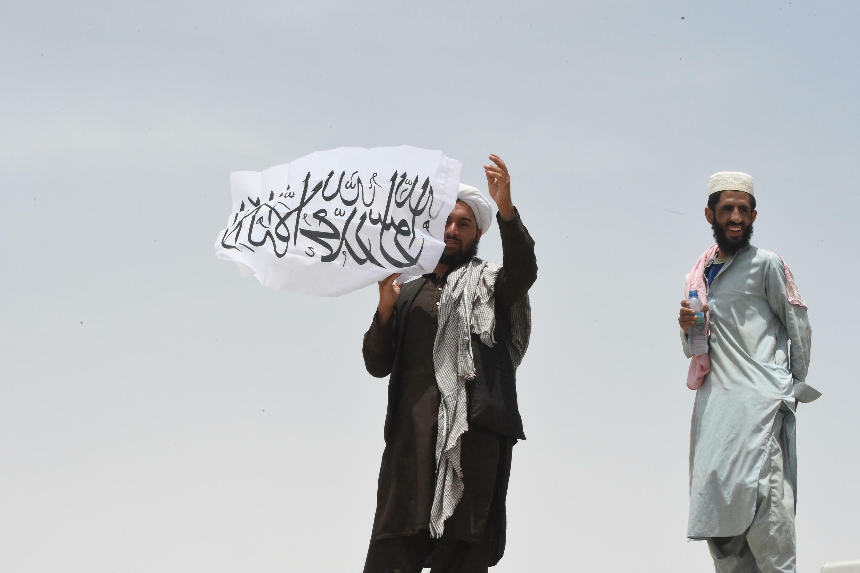 Un hombre enarbola la bandera taliban en el lado afgano tras cruzar el paso fronterizo situado en la ciudad paquistaní de Chaman, el 17 de julio de 2021, después de que Pakistán lo reabrió parcialmente
