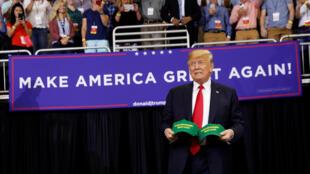 """Tổng thống Donald Trump cầm hai chiếc mũ có ghi """"Làm cho các chủ trang trại Mỹ lớn mạnh trở lại"""" trong cuộc mít-tinh ở Evansville, Indiana, ngày 30/08/2018"""