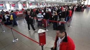 Passengers queue at Sydney's domestic airport on Monday