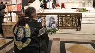 A fan takes a picture during a mass in tribute to French rock singer Johnny Hallyday in Paris on 9 December 2018 one year after Johnny's death.
