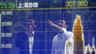 Tokyo businessmen react as they are reflected on a graph showing recent movements of Shanghai Stock Exchange B share index outside a brokerage in Tokyo, Japan, September 29, 2015.