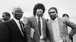 La famille Noah en 1983, lors d'un voyage à Yaoundé avec le président Mitterrand, à l'apogée de la carrière de Yannick. A sa gauche, son père Zacharie. A sa droite, son grand-père Simon.