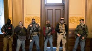 Des membres d'une milice, dont certains viennent d'être inculpés dans un complot visant à enlever la gouverneure du Michigan, devant le bureau de son bureau lors d'un vote pour approuver la prolongation de l'état d'urgence le 20 avril dernier.