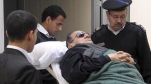 O ex-ditador Hosni Mubarak chega ao tribunal de maca, nesta segunda-feira.
