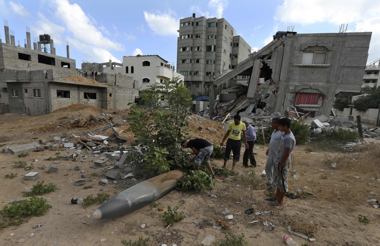 Người dân Palestine trước một căn nhà bị oanh kích ở dải Gaza, ngày 14/07/2014.