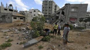 Palestinos diante de uma casa destruída por ataques de Israel, em Gaza (14/07/14).