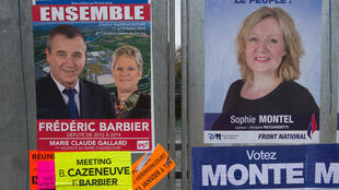 Posters supporting Socialist  candidate Frédéric Barbier (L) and the Front National's Sophie Montel in the Doubs by-election