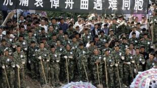 Des soldats chinois posent leurs pelles afin de respecter les trois minutes de silence en hommage aux victimes des glissements de terrain, 15 août 2010