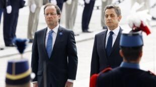 François Hollande et Nicolas Sarkozy devant la tombe du soldat inconnu, à l'Arc de Triomphe, à Paris le 8 mai 2012.