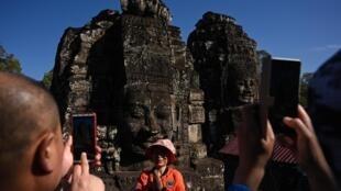 Un touriste chinois lors d'une visite du temple Bayon du XIIème siècle au complexe d'Angkor à Siem Reap, au Cambodge, le 6 décembre 2019.