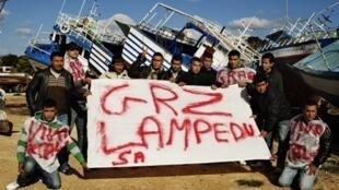 Des migrants tunisiens arrivés ces derniers jours à Lampedusa posent avec une banderole où l'on peut lire « Merci Lampedusa », le 15 février 2011.