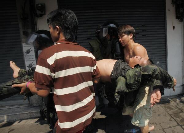 Soldados y civiles transportan a un uniformado herido durante las protestas del 10 de abril.