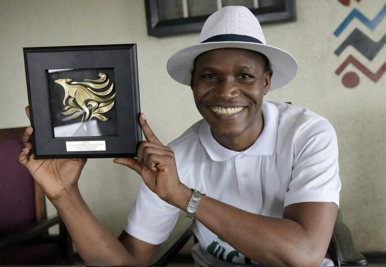 Nigeria's Wellington Jighere holds his World English-language Scrabble Champion award in Lagos on 10 November, 2015.