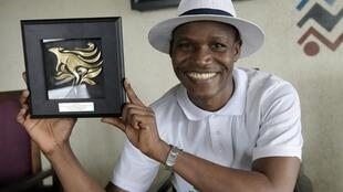Nigeria's Wellington Jighere holds his World English-language Scrabble Champion award in Lagos on 10 November, 2015.
