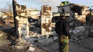韩国延坪岛遭朝鲜炮击后,一名男子面对废墟 2010年11月24日