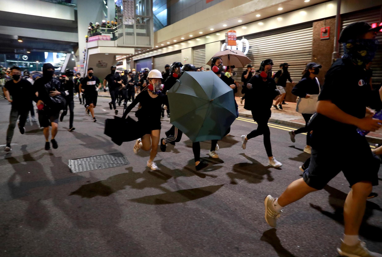 Manifestantes correm da polícia com guarda-chuvas em punho, em novo protesto em Hong Kong.