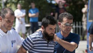 Des policiers kosovars escortent un prisonnier suspecté d'avoir des liens avec des groupes extrémistes syriens.
