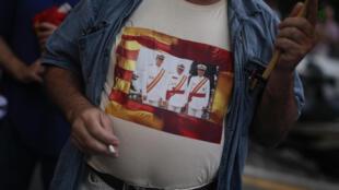 Un homme porte un tee-shirt où figurent le roi d'Espagne Felipe VI (à gauche), le dictateur Franco (au centre) et l'ancien roi d'Espagne Juan Carlos Ier (à droite) lors d'une manifestation organisée par le parti d'extrême droite espagnol Vox.
